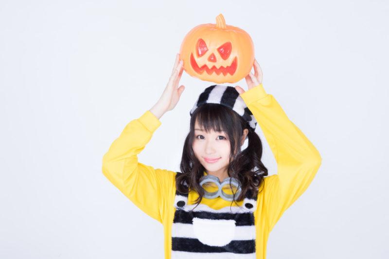 ハロウィンのかぼちゃお化けを持ち上げる仮装女子