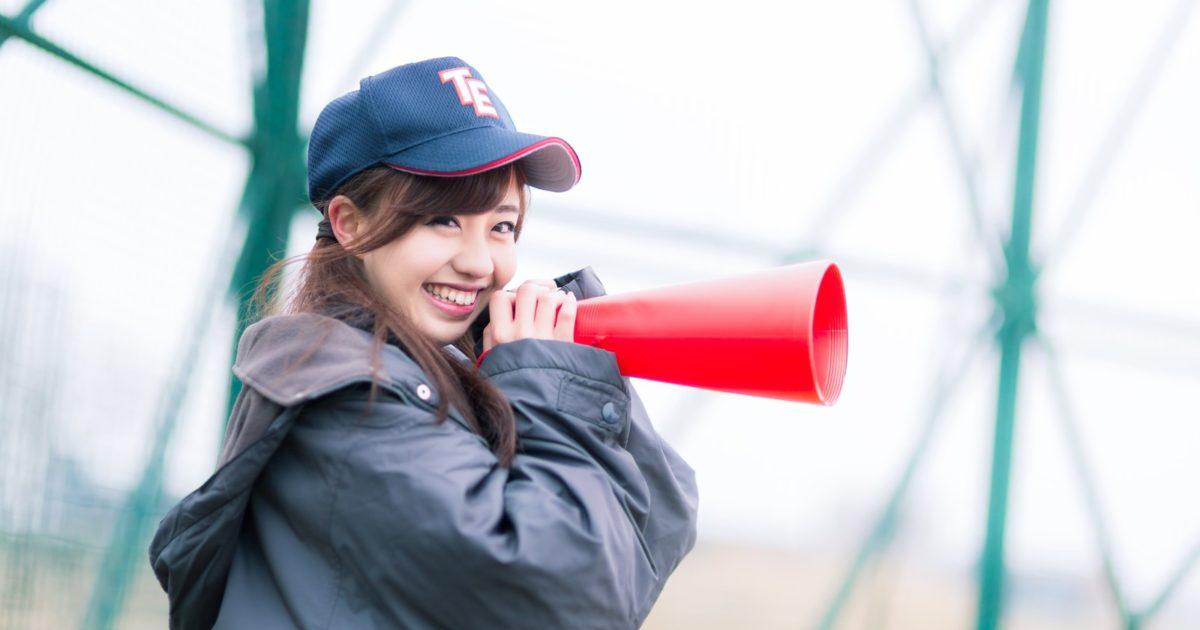笑顔で野球の応援をする女子
