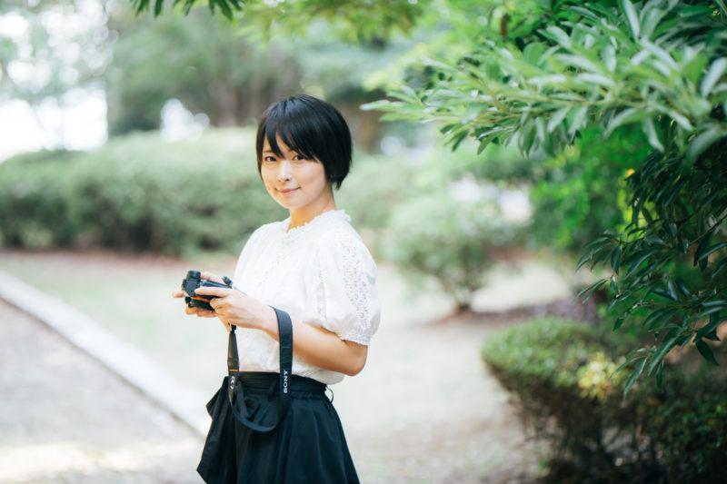 笑顔で会釈するカメラ女子