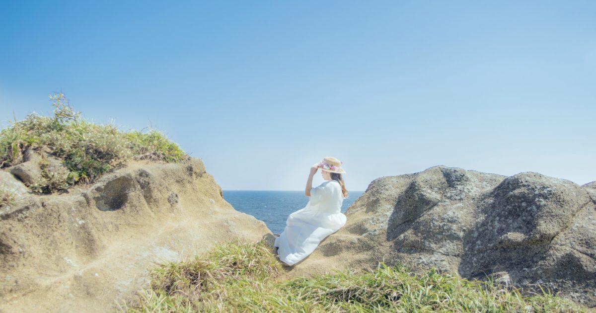 海岸に腰を下ろし海を見つめる女性