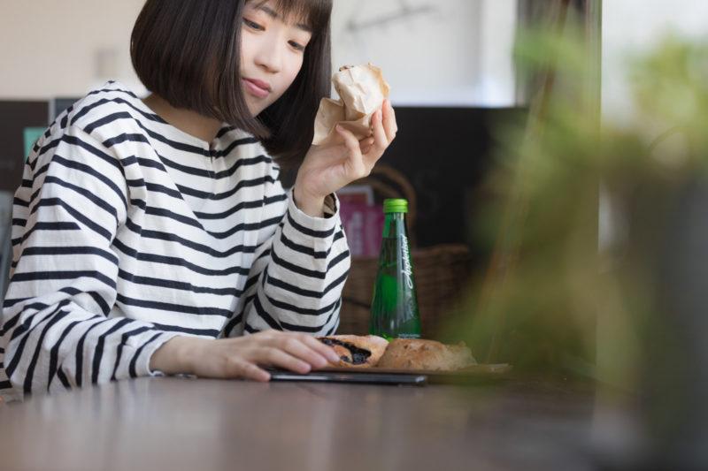 パンを食べながらスマホで売上をチェックする女性