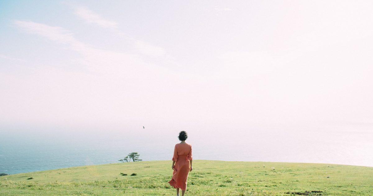 海を眺めて佇む女性