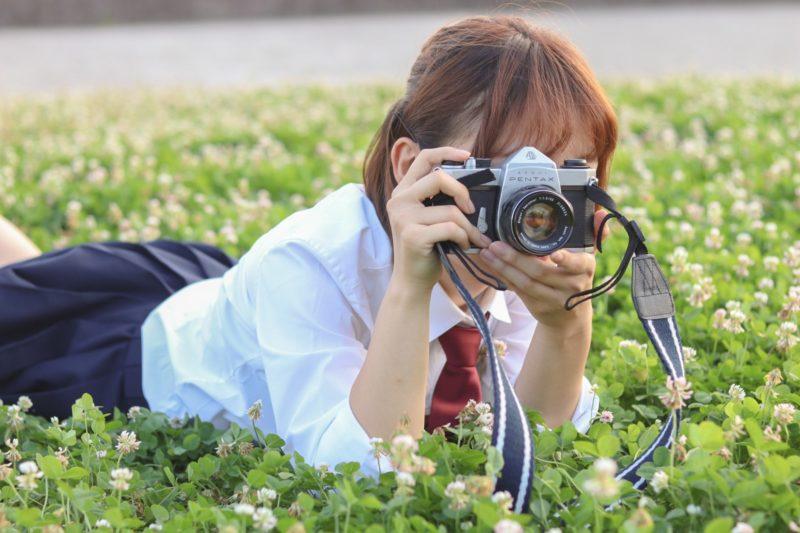 草原にうつ伏せてカメラを構える女子高生