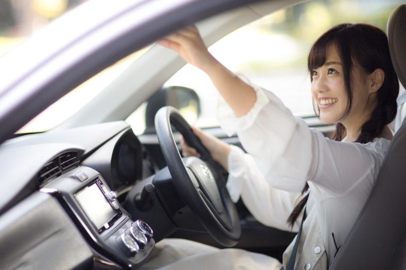 車内のバックミラーを調整する女子