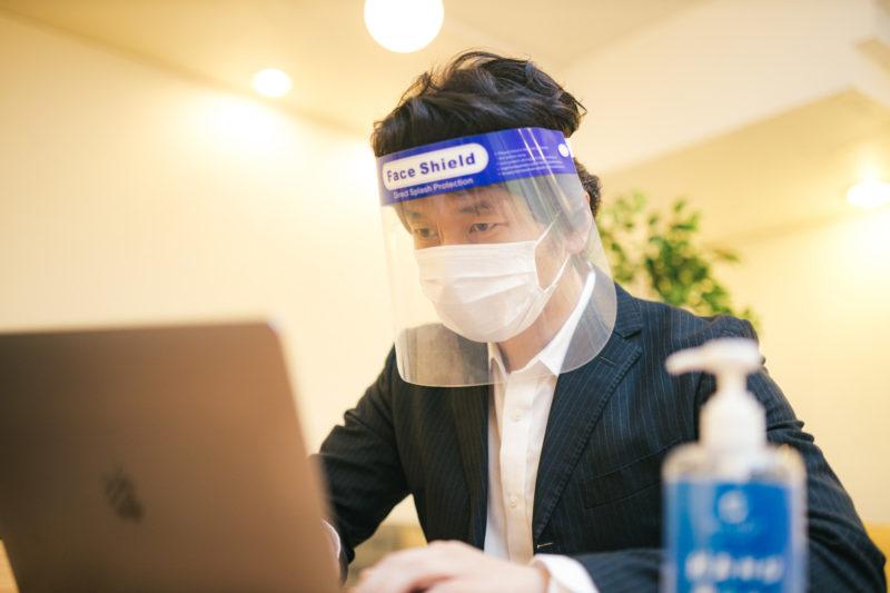 オンライン会議中もフェイスシールドとマスクを装着する男性