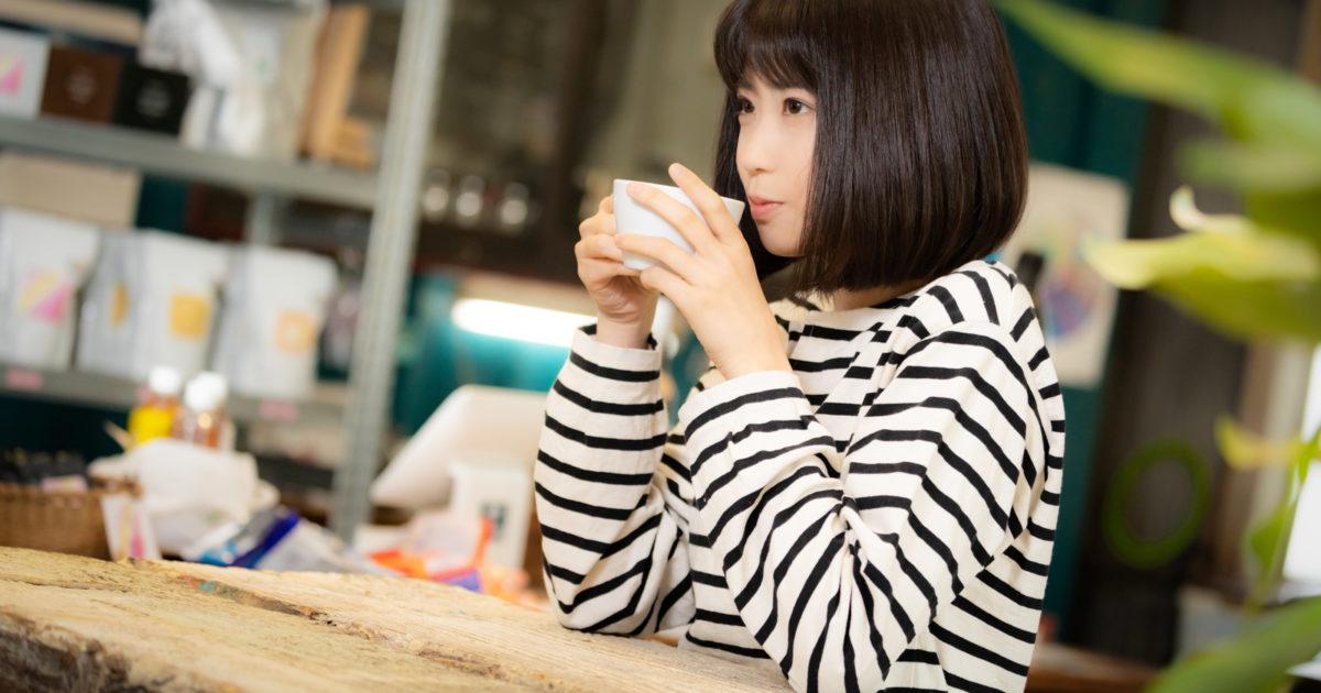 挽きたてのコーヒーを飲む女性