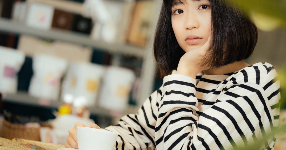 カフェで退屈そうにこちらを見つめる女性