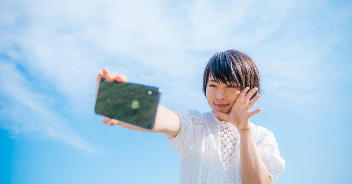 青空の下でスマホで自撮りする女子